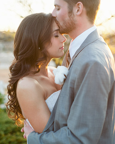groom kissing the bride on the forehead, sunset wedding photo