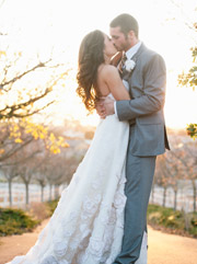photo of bride and groom kissing with the sun setting behind