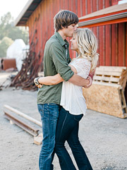 Couple embracing by the abandoned railroad cars