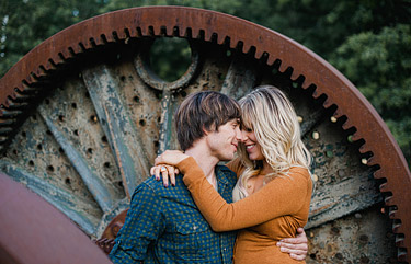 Couple embracing each other in front of a large industrial rusted wheel