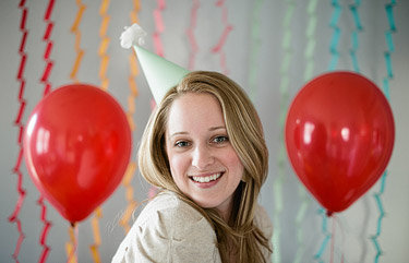 Portrait of a girl with a green party hat and red balloons and streamers