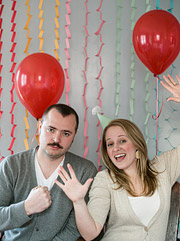 Portrait of a couple with red helium balloons and streamers in the background