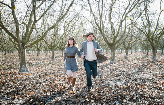 man and woman running through the apple orchard in the fall