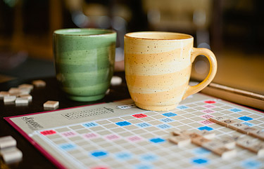 Tea mugs on top of Scrabble game