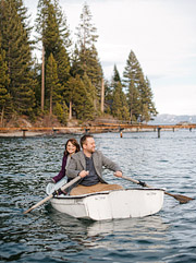 Engaged couple rowing the boat on Lake Tahoe with tree line in the background