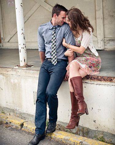 Couple snuggled up on the loading dock. He is wearing a buttoned up shirt with a tie and she is wearing a dress and brown leather boots