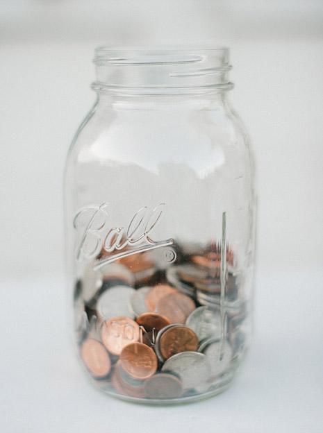 White Mason Ball jar half way filled up with change