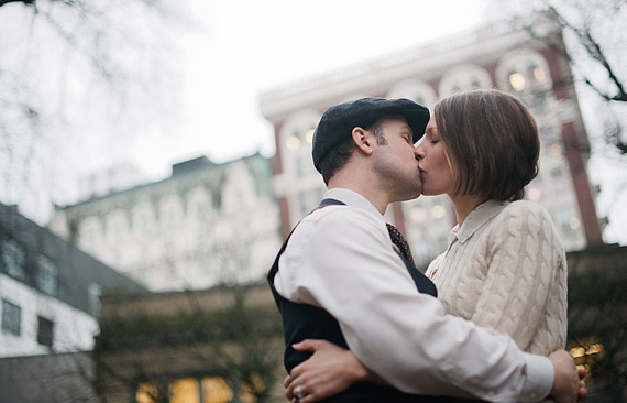 Couple kissing with Portland, OR downtown buildings in the background
