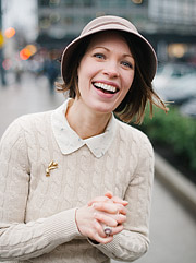 Photo of a woman laughing wearing a vintage har and a broche