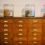 3 jars with rubber bands, paper clips and erasers on top of the cabinet with drawers