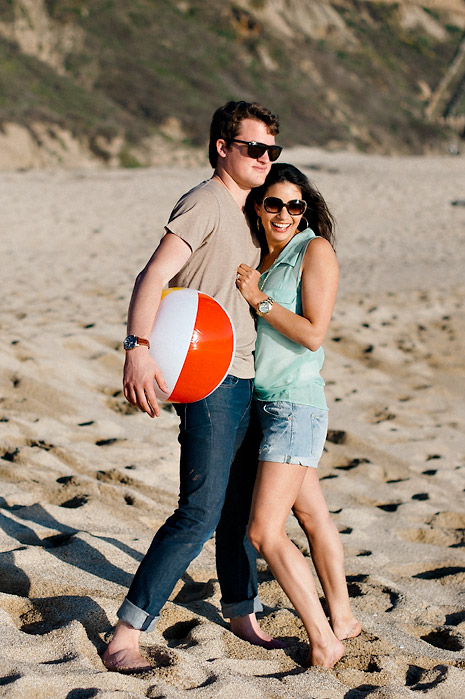 Husband holding his wife in one hand and beach ball in another.