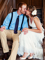 Bride and groom with suspenders sitting on the church steps.