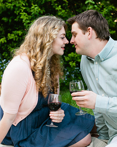 Guy and girl holding wine glasses and getting ready to kiss