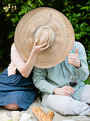 Couple hiding behind the wide brimmed straw hat (probably making out) with thumbs up