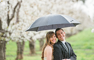 Bride and groom under the umbrella with raindrops in the foreground