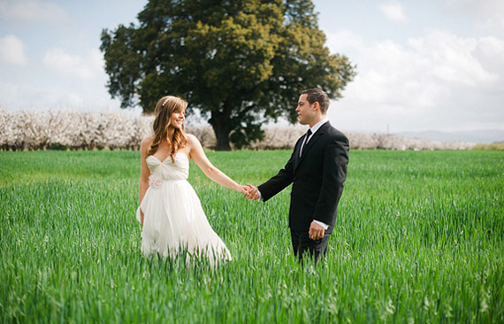 Bride and groom standing in the green field wearing Sarah Seven dress.