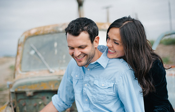 Couple laughing in front of a rusted vintage truck