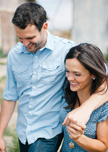 Guy has his arm around a girl while walking together and smiling