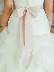 Beautiful pastel pink bow on the back of the bride's dress