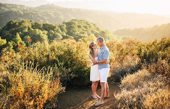 Golden light and rolling hills. Engaged couple hugging each other.