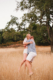 Girl giggling as her fiance picks her up. Goldne grass and an old tree in the background.