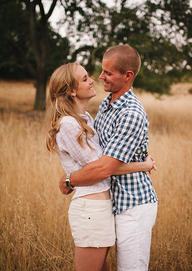 Couple wearing white summer shorts hugging each other. Engagement photography in the golden hills.