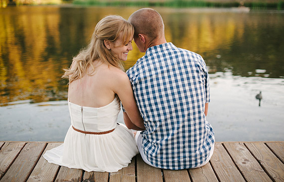 Portraiit of an engaged couple sitting on the dock of a lake snuggling together. Engagement portrait.
