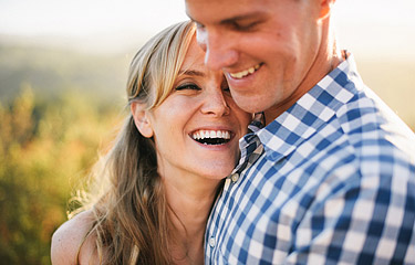Closeup of a guy and a girl laughing together.