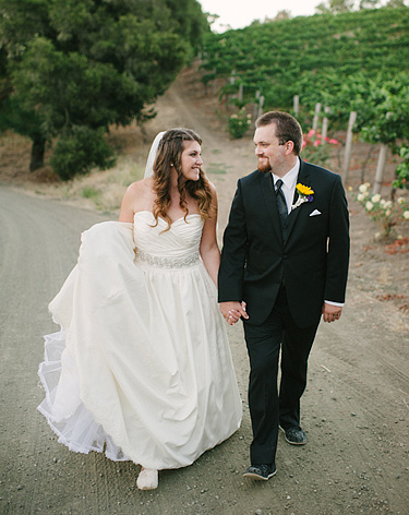 Bride and groom walking together on a dirt road next to a vineyard at Thomas Fogarty Winery In Woodside, CA