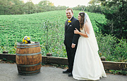 Portrait of bride and groom next to a wine barrel with a vineyard in the background at Thomas Fogarty Winery In Woodside, CA