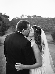 Black and white photo of a bride kissing the groom