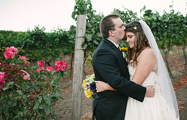 Groom kissing the bride on the forehead at Thomas Fogarty Winery vineyard
