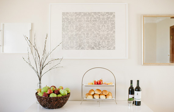 Pears, snacks and wine arranged on top of a white dresser