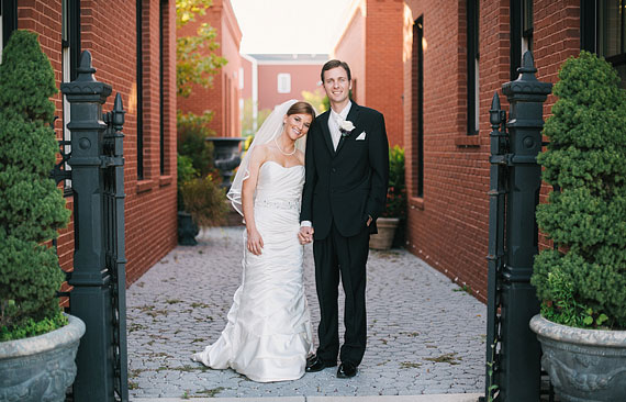 St. Louis weding photography in New Town by St. Charles, MO Bride and groom standing in an alley with red brick walls.