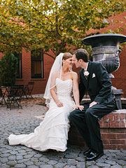 Bride and Groom surrounded by red brick walls by tht water fountain in New Town, MO
