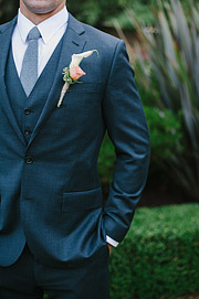 Close up photo of groom's suit. Jacket, vest and a tie with boutenir.