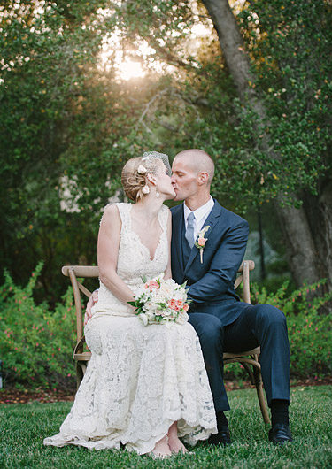 Bride and groom sitting on two chairs kissing each other with golden light form the sunset. Wedding photography in Woodside, CA