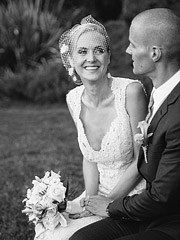 Black and white image of the bride sitting next to the groom smiling.