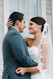 Beautiful portrait of bride and groom in front of the white presidio building in San Francisco, CA