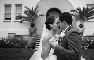 Black and white photo of bride and groom dancing in front of the Film Centre in the Presidio, San Francisco, CA