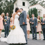 Bride and groom kissing with bridal party in the background laughing. Main Post Chapel wedding ceremony venue.