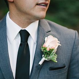 Close up detail of the groom. Pale pink rose boutonniere on gray suit.