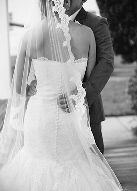 Groom holding the bride with a beautiful lace veil hanging on bride's shoulders