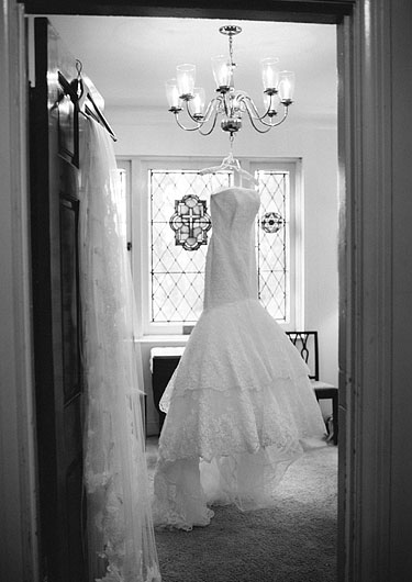 Black and white shot of the mermaid wedding dress hanging from a chandelier.