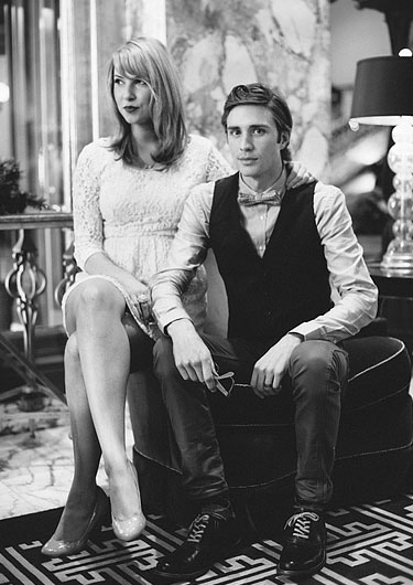 Balck and white photo of a dressed up couple sitting next to each other