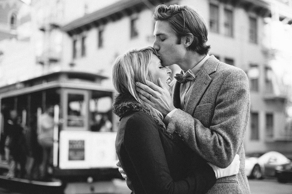 1950s inspired brian gently kissing shayla on the forehead with cable car in the background san francisco