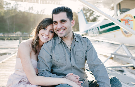 Engaged couple sitting on the dock in front of a seaplane