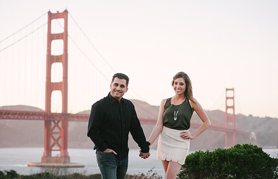 Couple holding hands in front of the Golden Gate Bridge.