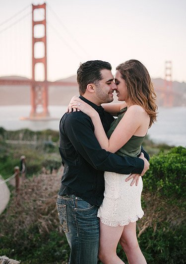 Couple cuddling in front of Golden Gate Bridge