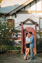 Couple kissing in front of a red wooden gate, San Mateo engagement photography.